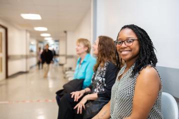 Three women sat waiting in a hospital corridor