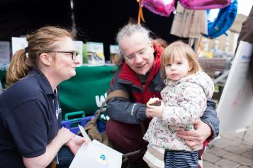 Healthwatch volunteer speaking to a grandparent and child at an event