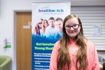Young girl standing in front of a Healthwatch banner