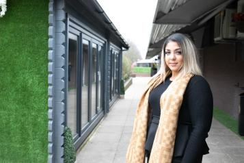 Woman stood outside in a courtyard wearing a bright scarf