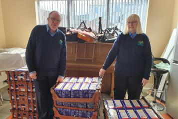 Image of Brian Jones, CEO of The Moses Project with wife Stella and pallets of food
