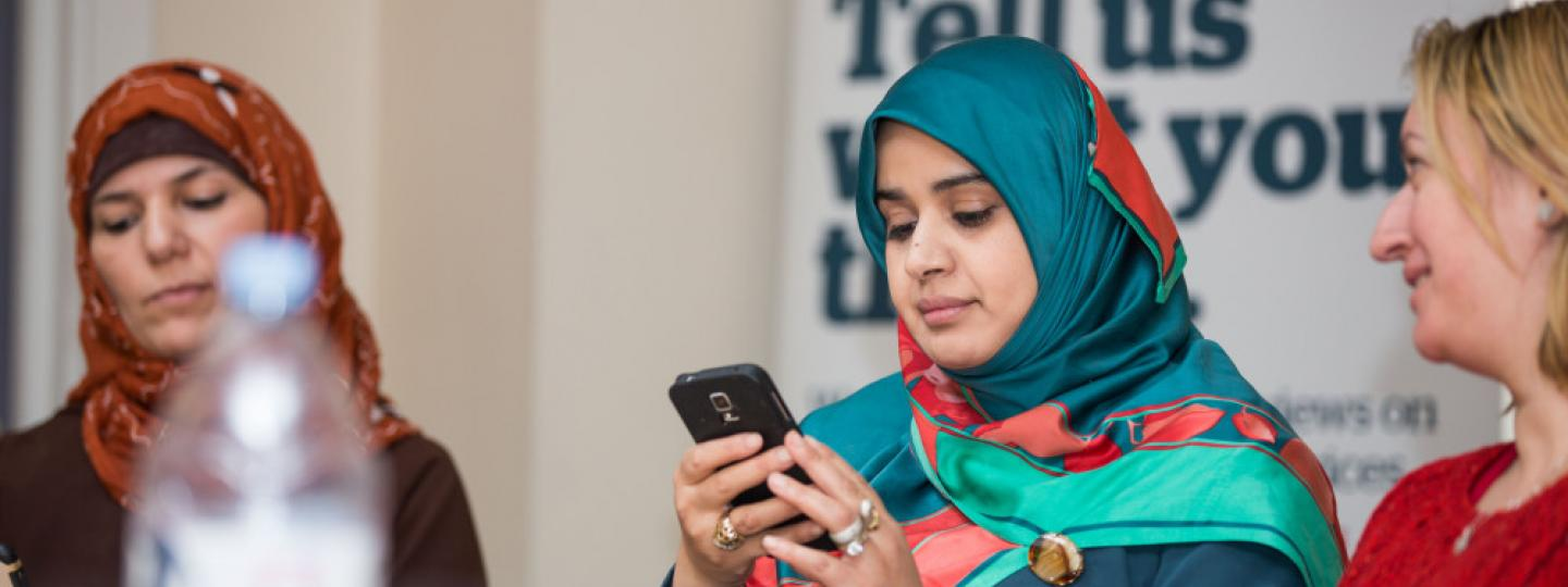 Image of woman on mobile phone with other people