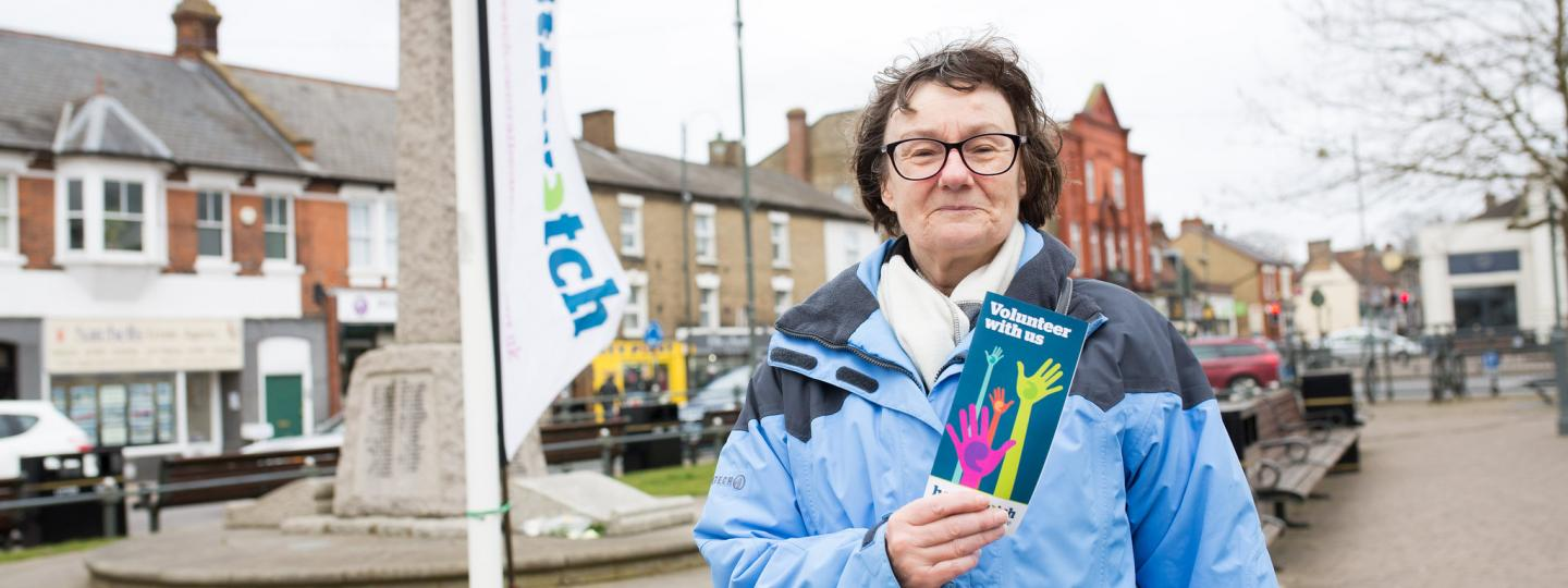Woman holding a volunteering leaflet stood in front of a Healthwatch banner