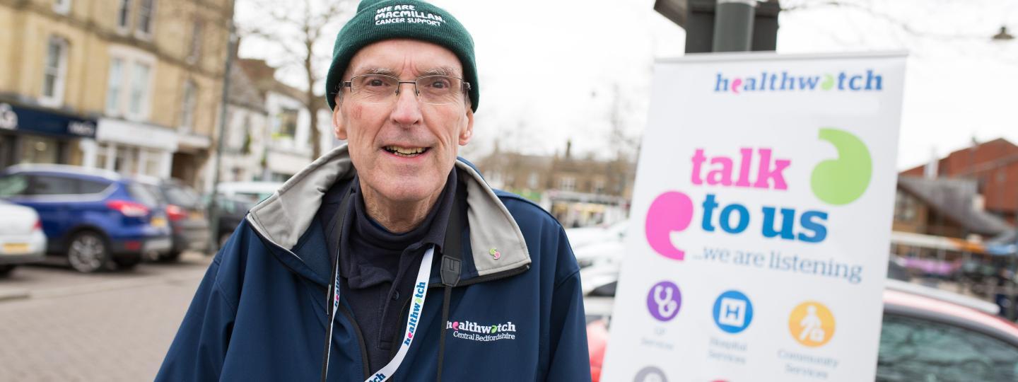 Man in front of Healthwatch banner